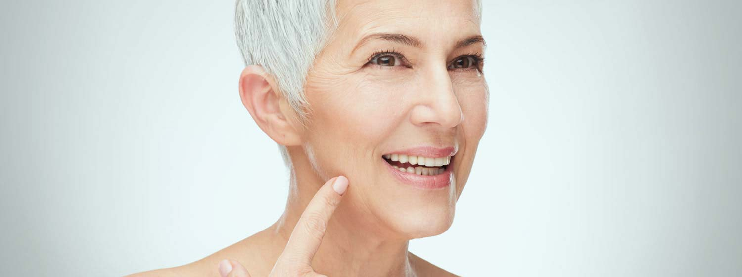 woman pointing to face for spot removal